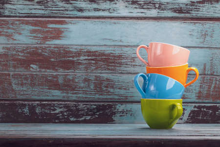 Vintage tone colorful coffee cups with copy space on wood board , stack coffee cup Archivio Fotografico