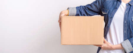 Asian delivering package with brown box isolated on grey background , Closeup hands of delivery holding package to deliver