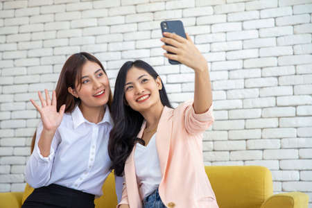 Happy beautiful young asian woman friendship selfie together , Happiness teenagers taking pictures selfie in living room