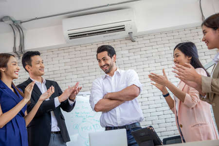 Team of business applauding their leader after success on business in office and discussing documents and ideas report at meeting , Discussion strategy group working concept Archivio Fotografico