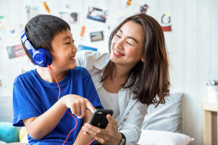 Beautiful asia woman and her son play with digital smartphone and smiling happy in living room