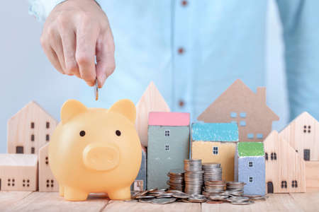 Businessman save money on piggy bank , Planning for the future of rent for an apartment or home concept .Hand put money coin into piggy bank for save for home