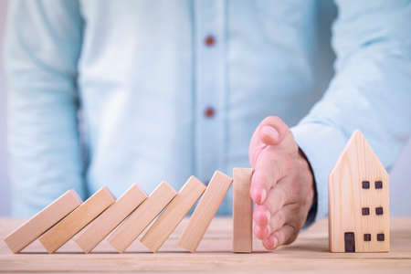 Business hands stop wooden blocks of domino effect before destroy house , Private property protection finance from domino effect concept