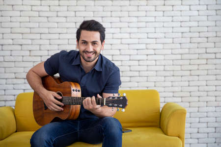 Lifestyle portrait of attractive handsome man with pleasant smile relaxing and sitting play guitar at living room