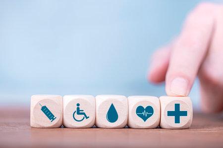 Businessman chooses a emoticon icons healthcare medical symbol on wooden block , Healthcare and medical Insurance concept Archivio Fotografico