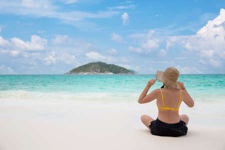 Woman bikini relaxing from behind wearing sun straw hat on beach looking at ocean in a tropical , Summer holiday travel concept