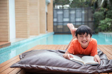 Portrait Happy boy reading a book lying on the bed pillow , education reading concept