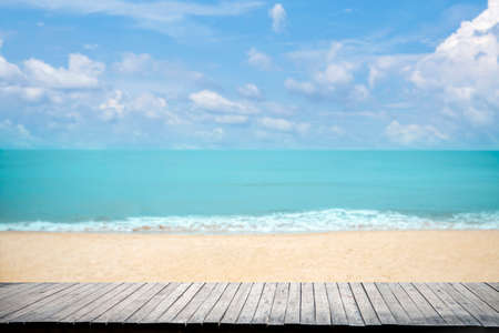 Close up wooden table top on sandy beach blue sea and tropical beach , Summer holiday concept.