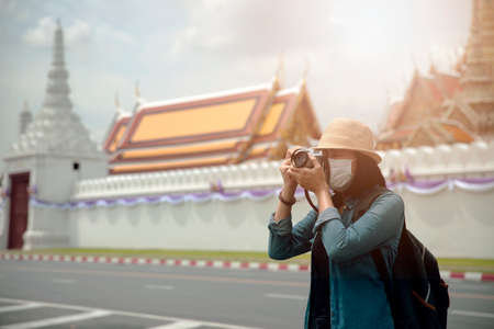 Asian women wearing surgical face mask traveler with camera travel of lifestyle portrait , outdoor summer concept