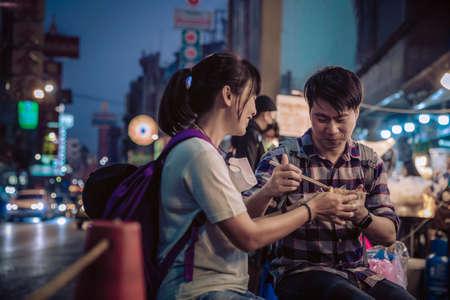 Asian couple eating in Street food Night market for tourist on chinatown at yaowarat road in bangkok
