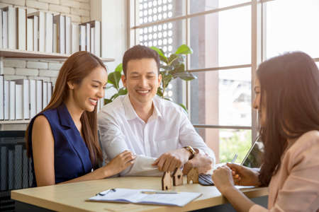 Happy young loving couple talking to their real estate agent with smile looking at house , Planning for the future of the family concept