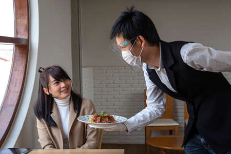 Smiling waitress serving an order of food , Waiter carrying plates wear a mask prevent the spread of virus Archivio Fotografico