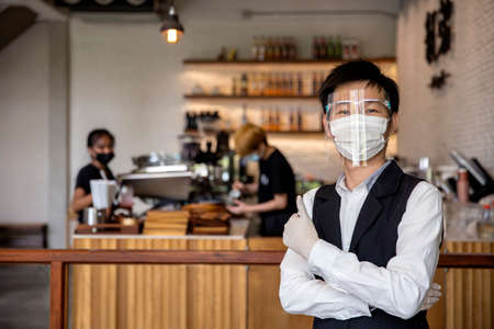 Coffee and restaurant shop owner expressed confidence in preventing , or the , by wearing a face mask and gloves. concept protect