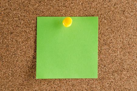 Single green paper sticker on a corkwood background.
