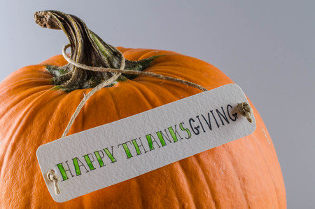 Pumpkin with a label on a gray background. Happy Thanksgiving.