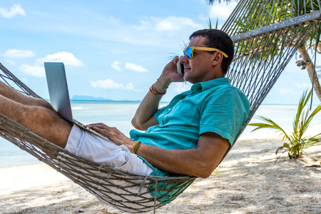 Man in a hammock on a tropical beach working on a laptop and talking on the phone