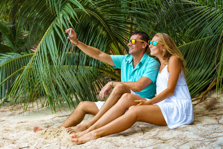 Young happy couple sunglasses with phone on a tropical beach