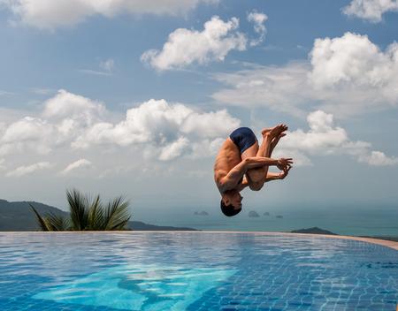 젊은 체육 남자가 산 꼭대기에있는 수영장으로 뛰어갑니다. 스톡 콘텐츠