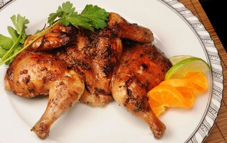 Roasted cornish game hen with orange and lime.