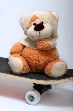 Injured teddy bear on his skateboard.