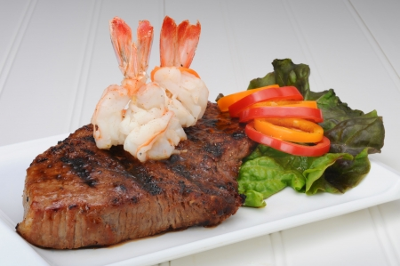 Steak with boiled shrimp on top.