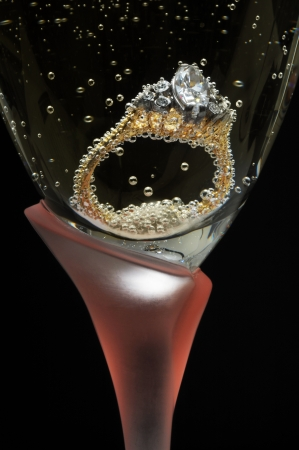 engagement ring: Diamond engagement ring in champagne glass. Stock Photo