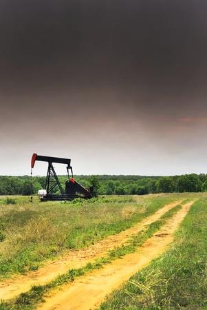 yacimiento petrolero: Pumper de pozos de petr�leo en el oeste de Texas tormenta. Foto de archivo