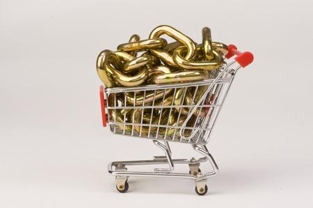 Shopping Cart Full of Golden Chains. Stock Photo - 12087746