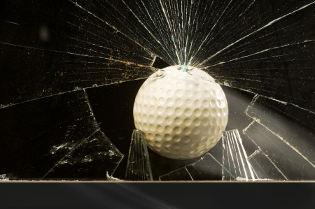 Balle de golf � travers la fen�tre en verre photo