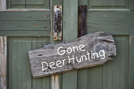 deer hunting: Gone deer hunting sign on old green door  Stock Photo