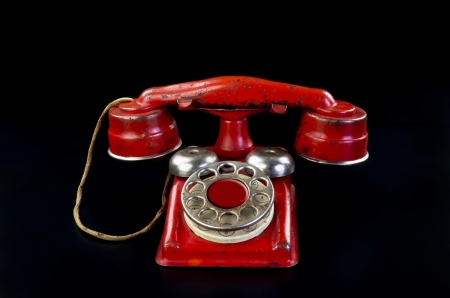 Old red rotary telephone. Stock Photo - 24924924