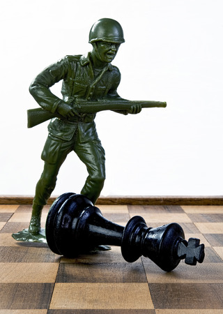 Toy soldier fighting chess King. Stock Photo