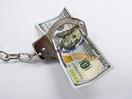 Cold hard cash in cold steel handcuffs. Stock Photo - 26158751