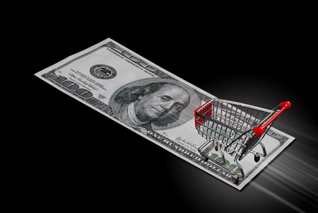 Shopping cart streaking across hundred dolllar bill. Stock Photo
