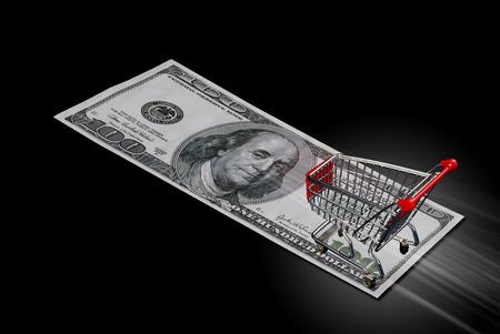 streaking: Shopping cart streaking across hundred dolllar bill. Stock Photo