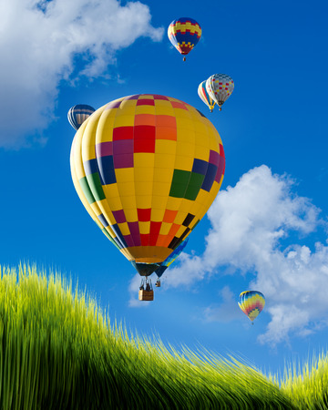 Hot air balloons flying high over green grass. Stockfoto