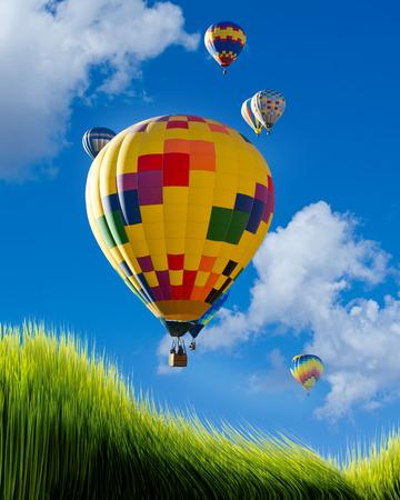adventure aeronautical: Hot air balloons flying high over green grass. Stock Photo