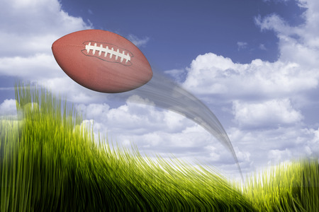 Football flying in air over green grass.