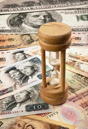 international money: Hour glass with world money and abundance.