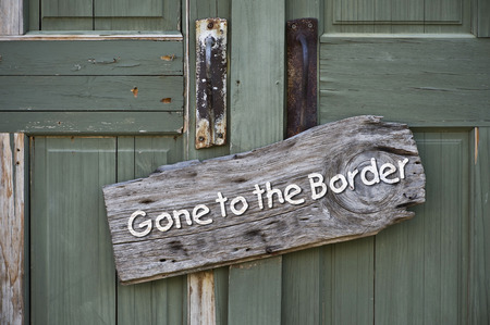 illegal immigrant: Gone to the border sign on old green door.