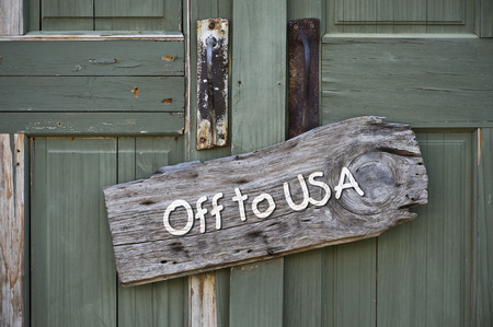 Off to USA sign on old green door. photo