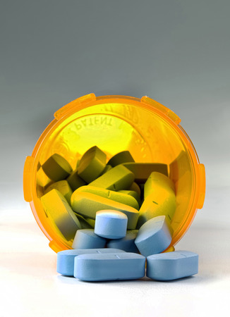 Little blue pills in a yellow pill container. Stock Photo