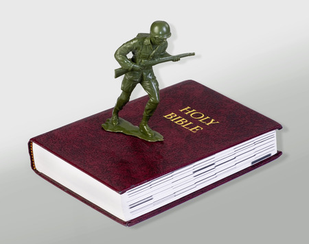Toy green soldier standing on bible.