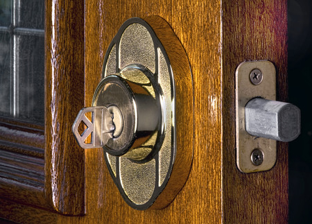 door bolt: Deadbolt lock on mahogany front door.