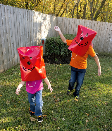Kids playing with funny red bag face.