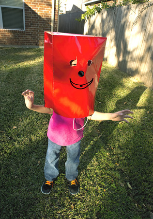 Kid playing with funny red bag face.