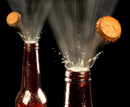 Beers popping spray and caps.. Stock Photo