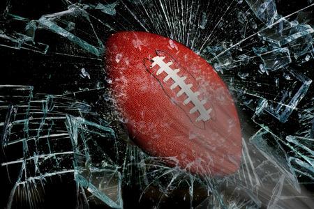pigskin: Fast football through broken glass. Stock Photo