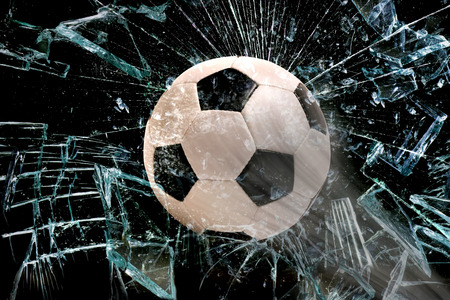 Fast Soccer ball through broken glass. Stock Photo