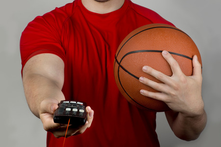 b ball: Holding tv romote control and basketball. Stock Photo